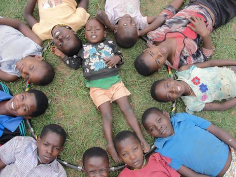 Kin kids laying in a circle