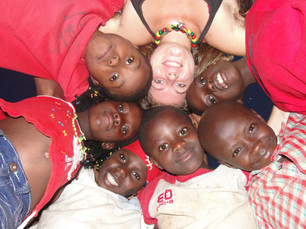 Kids standing in a circle with volunteer looking down at camera