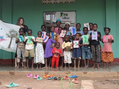 Kin kids and volunteer with footprint art