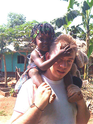 Volunteer with kin kid on shoulders