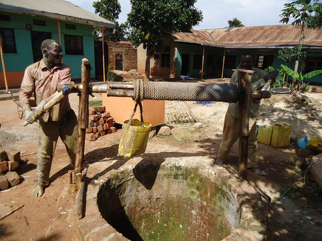 Kin staff working the well to get water to the community