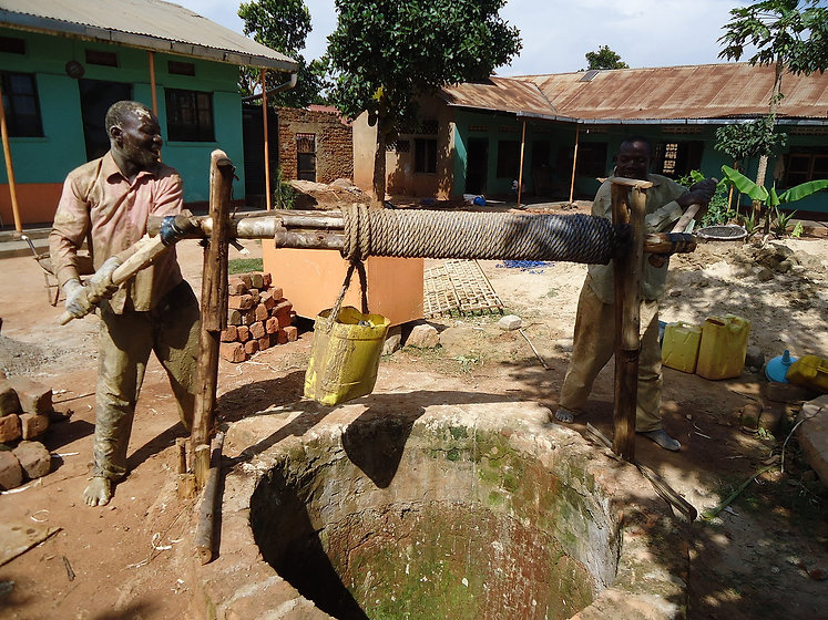 Kin staff working the well to supply water to the community