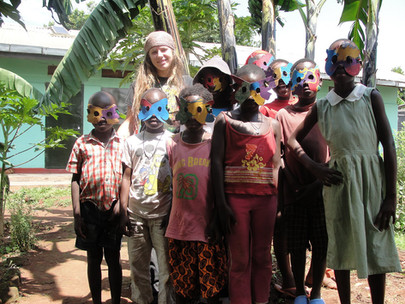 Volunteer and kids with masks made during craft time