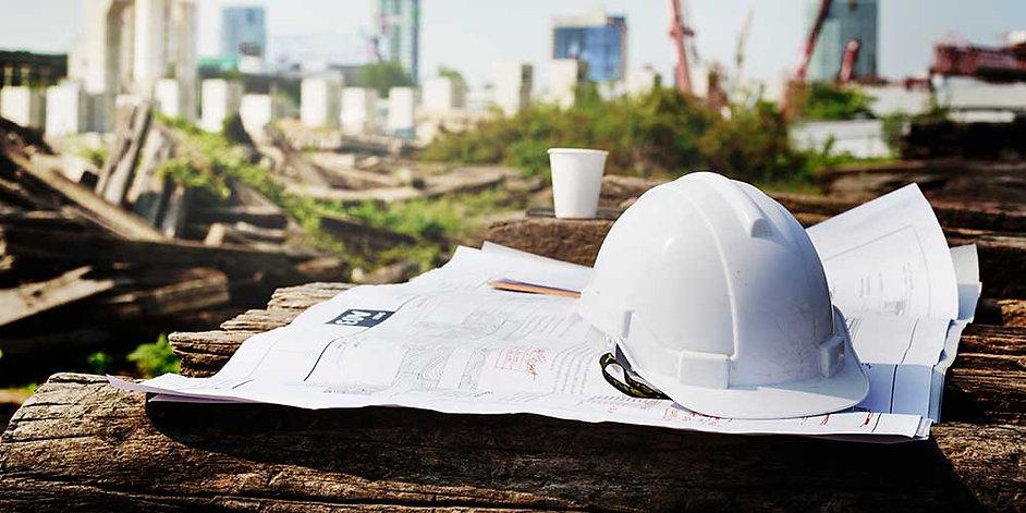 Fagtilsyn på byggeplads med projekttegning og sikkerhedshjelm