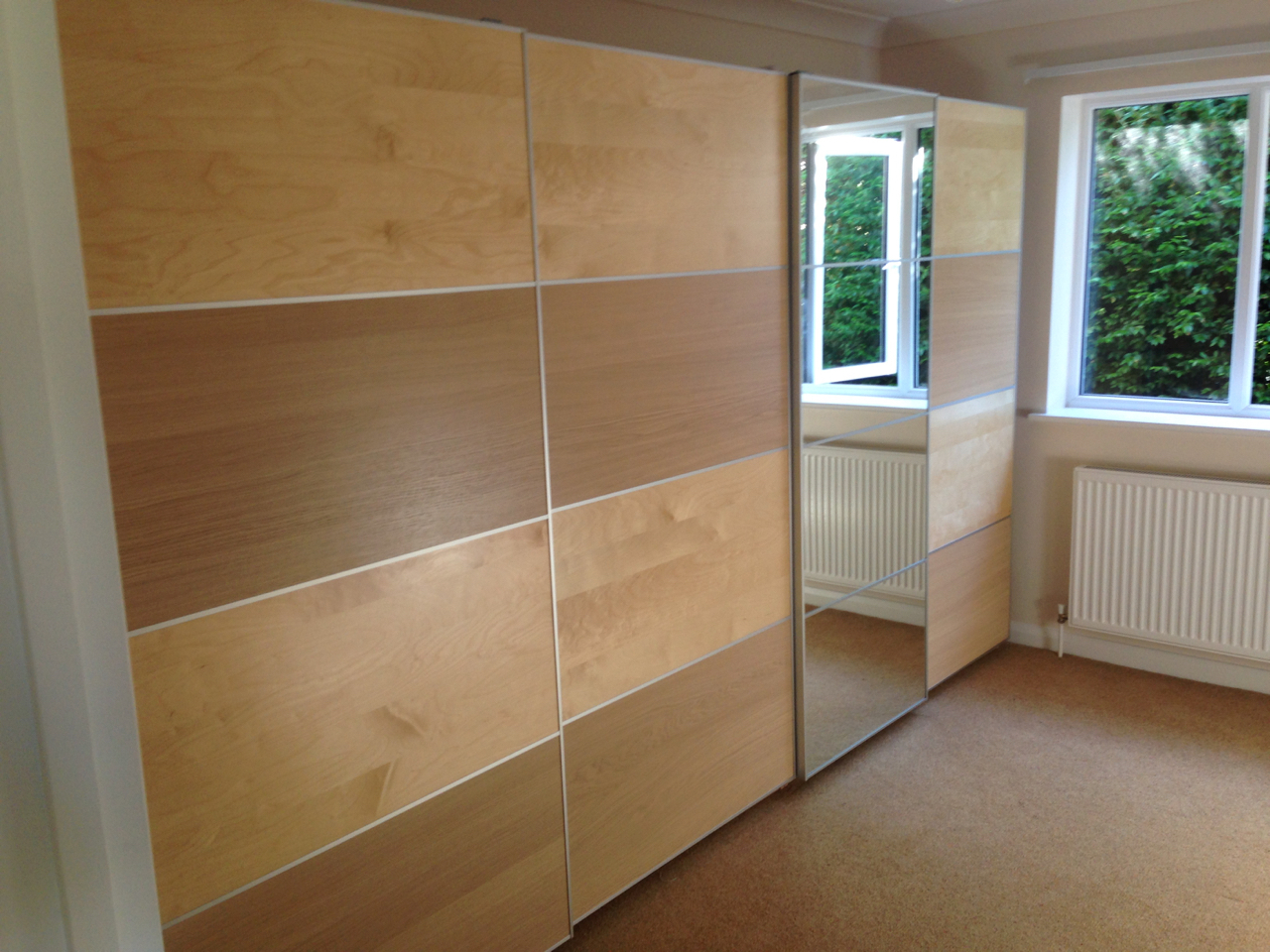 Ikea PAX sliding wardrobes with two wood types in doors assembled by www.norwichflatpack.co.uk