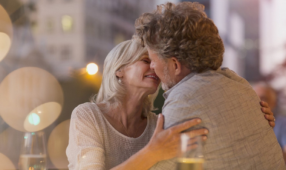 couple kissing across table in restauran