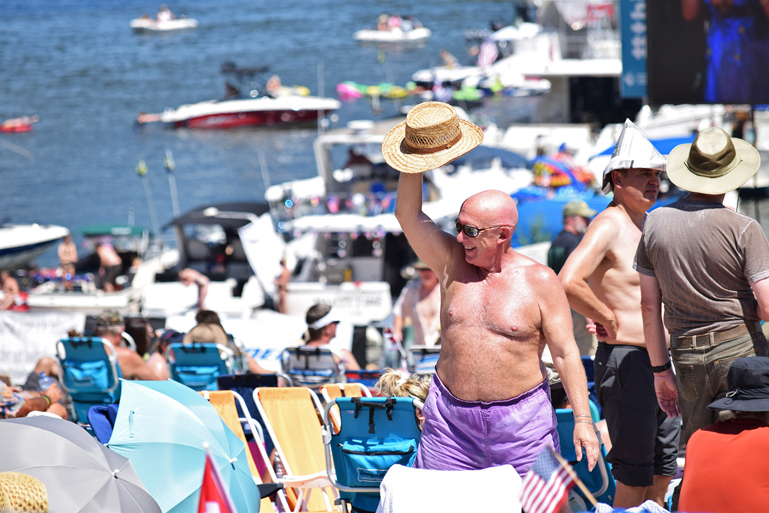 A joyful Blues Fest attendee waves their hat to fellow sunbathers on the shore of the Columbia River. Portland, Oregon.