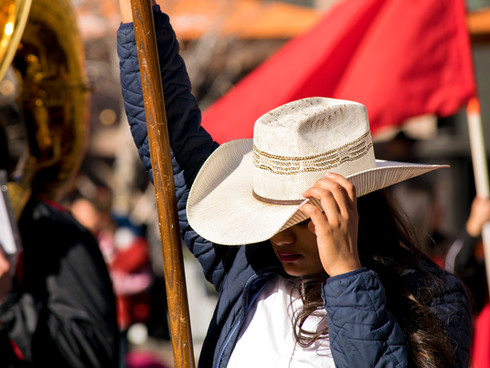High school flag holder adjusts their cowboy attire during the opening band numbers of the Western Stock Show Parade. January 11th, 2020. Denver, Co.