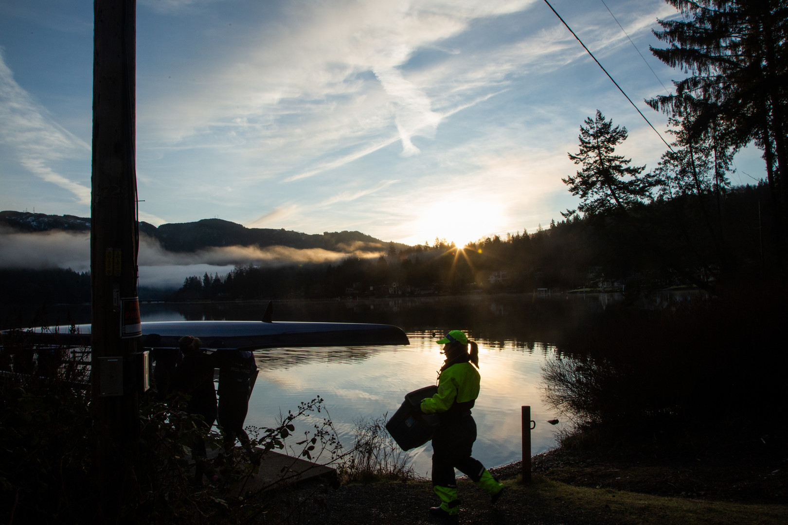 Jonah Bettger in full coxswain gear, follows her rowing team to the dock to prepare for early morning practice on Lake Samish, Washington.