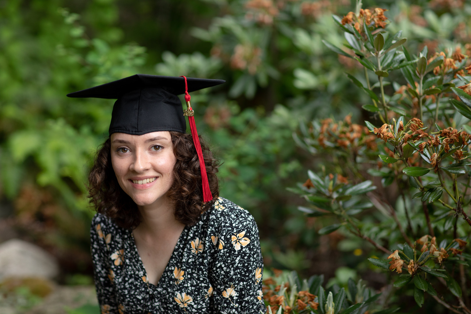 Emily Stout smiles among the Big Rock Garden greenery for her 2019 graduation photos. Emily frequents the garden that is near her house to read and admire the 20+ sculptures open to the public.
