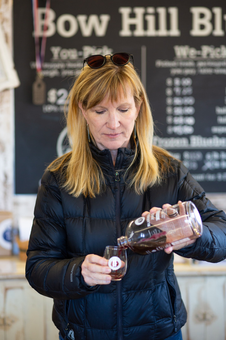 Susan Soltes, co-owner of Bow Hill Blueberries with her husband Harley, pours a shot of blueberry juice from their storefront in Bow, Washington. The Soltes took over the farm in 2011 after moving on from media jobs. Their farm as of 2020 is 73 years old.