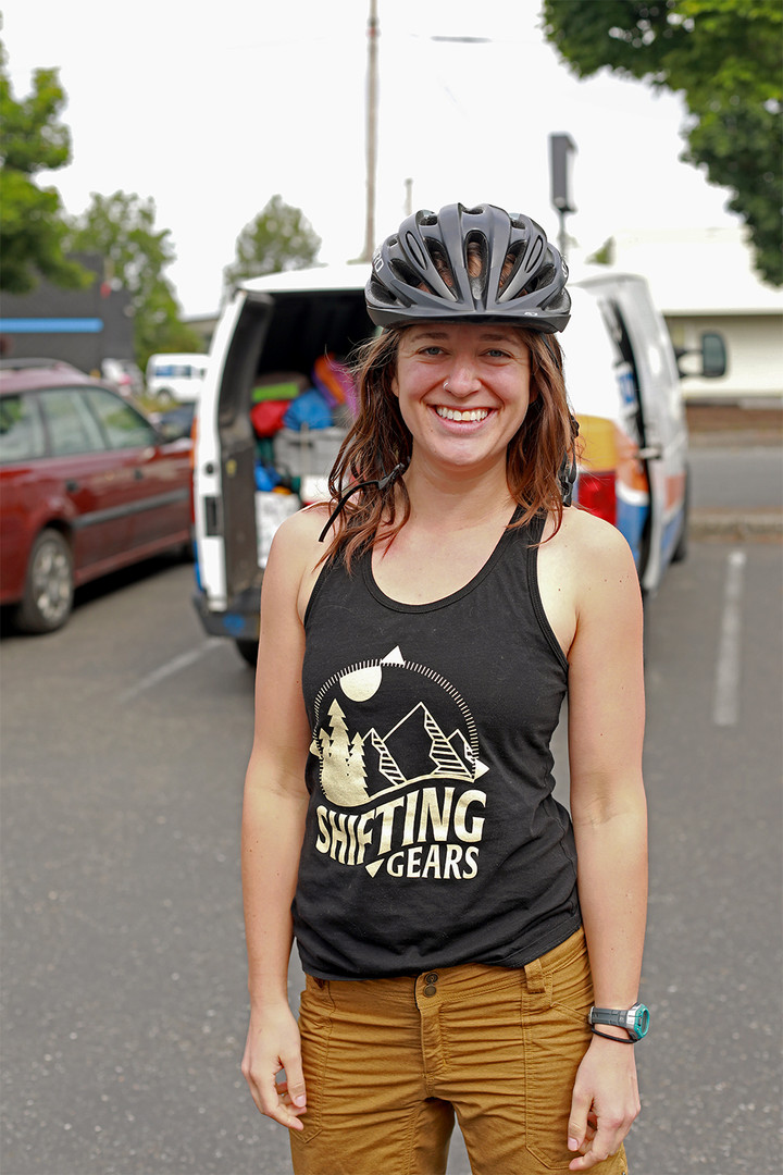 A Shifting Gears member in front of the van full of bike trip participant's gear. The group Shifting Gears is for womxn of all skills and backgrounds to join together to elevate their outdoor experiences through backpacking, biking, and all recreation. Bellingham, Washington, June 2019.