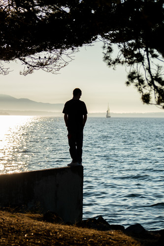 On top of the old boat launch in Boulevard Park, a pedestrian gazes down into the Bellingham Bay close to sunset. Bellingham, Washington.