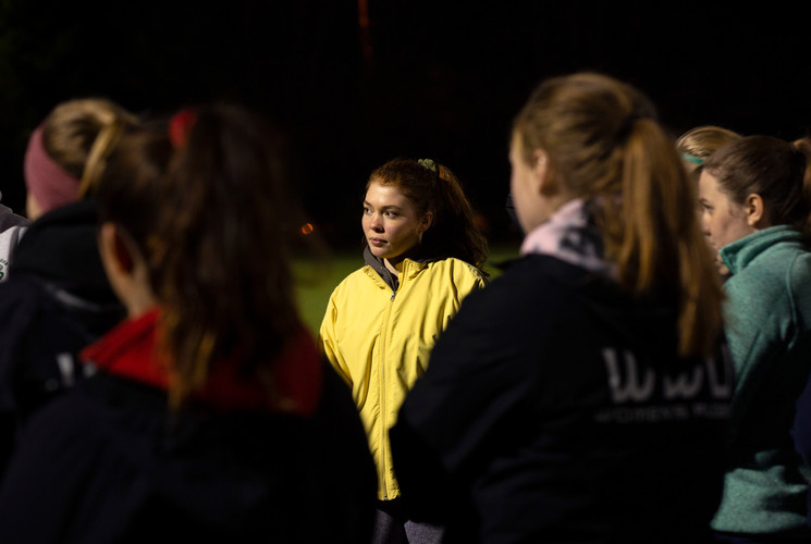 Western's women rugby team listens to their coach before an evening practice at Western Washington University. 2019.