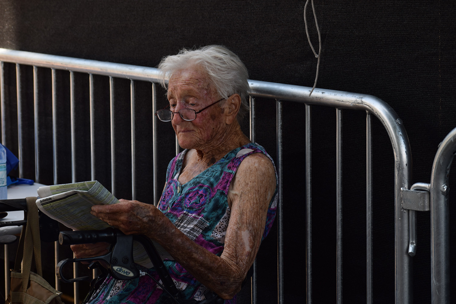 A festival-goer relaxes before the next musical performance with the day's newspaper. Portland, Oregon.