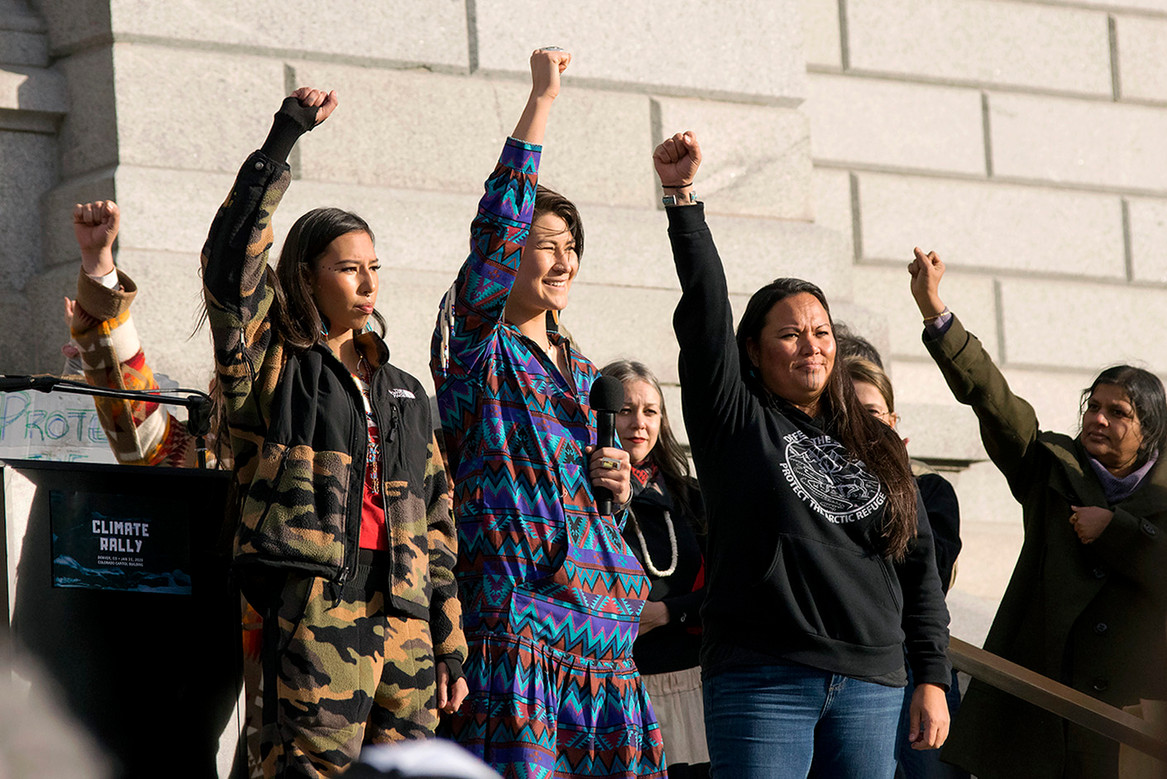 Speaker and Water Protector Deenaalee Hodgdon (middle) with her family beisde her leads climate change rally audience in a guided chant before raising their fists to the air. Capitol Hill. January 31, 2020. Capitol Hill, Denver, CO.