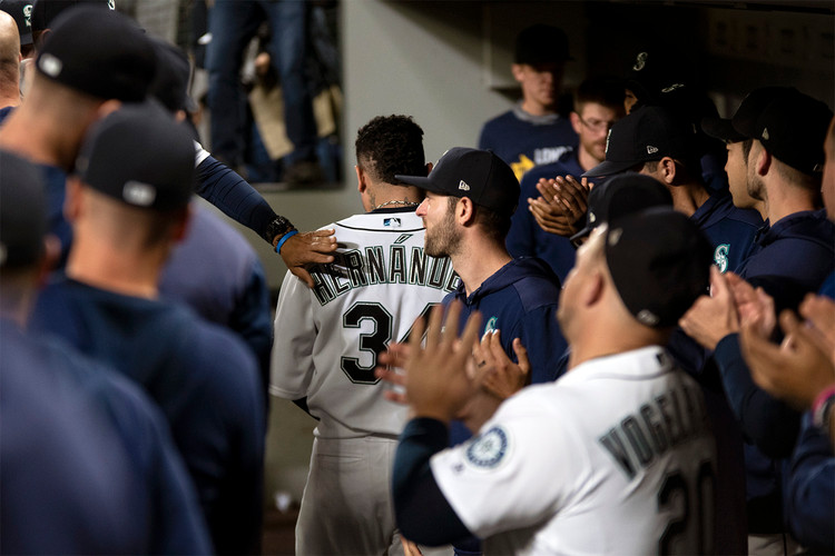 A teammate reaches down into the dugout to give pitcher Felix Hernandez a pat on the back before he addresses his fans at the end of his final game. Seattle, WA. September 27, 2019.