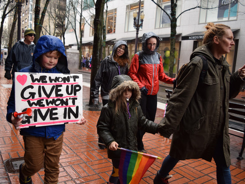 """A family with two children walks to the meeting location for The Women's March in Portland, Oregon. One child holds a sign saying """"We Won't Give Up, We Won't Give In"""". 2017."""