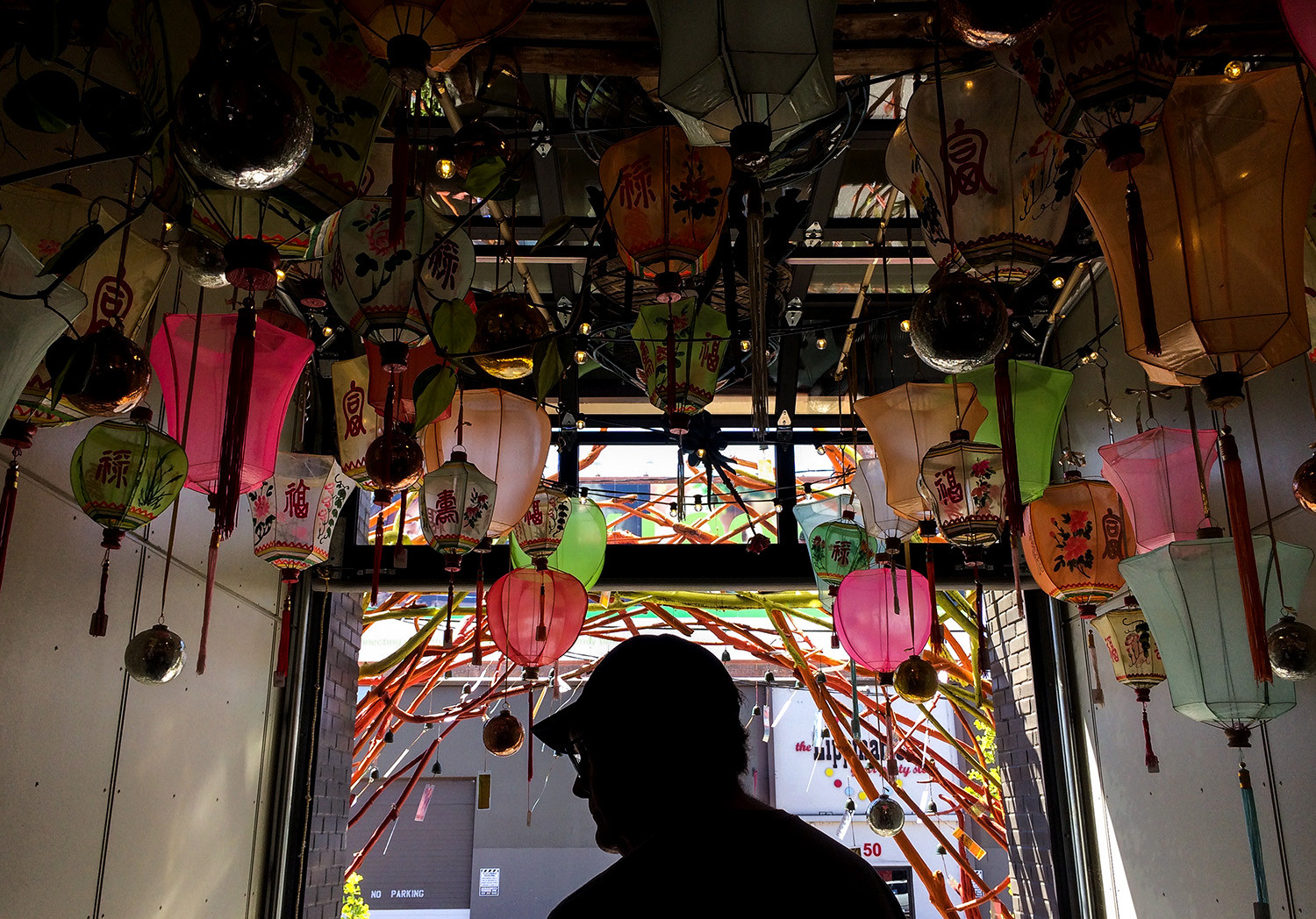A customer of Cargo in southeast Portland takes one last look at wares before exiting under the lantern display. Portland, OR. 2017.