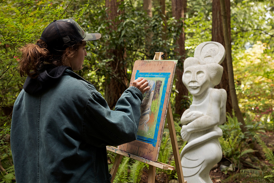 An artist uses the Natura sculpture to create an oil pastel portrait. Big Rock Garden hosts a public, free Mothers Day event that invites local artists to create works onsite of the art, then sell them to visitors. May 12, 2019. Bellingham, WA.