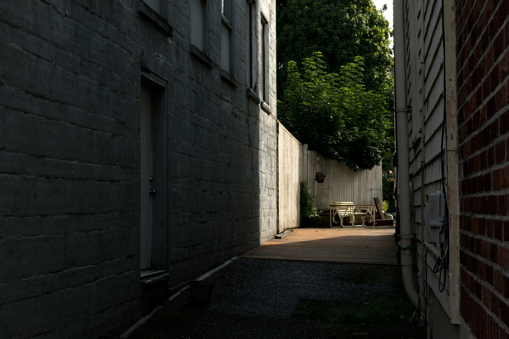 An shadowed alleyway with a lit bench around the corner in Astoria, Oregon. 2019.