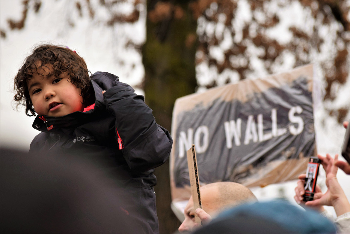 A child sitting atop shoulders in front of signage at the inaugural Women's March. March 11, 2017. Portland, OR.