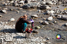Woman washing her clothes in the river,
