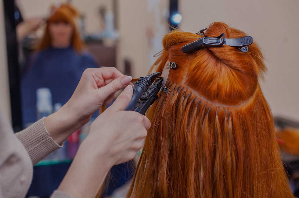 Copy of The hairdresser does hair extensions to a young, red-haired girl, in a beauty salo