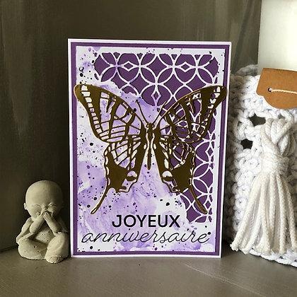 Carte ''Joyeux anniversaire'' avec un grand papillondoré sur fonds violet.