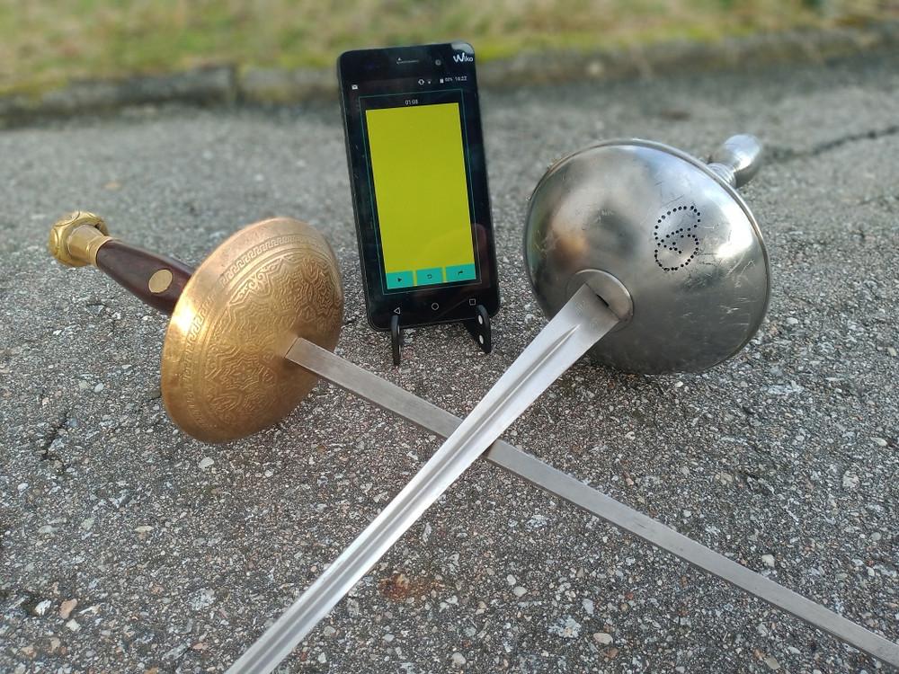 Zwei gekreuzte Degen mit einem Handy im Hintergrund.