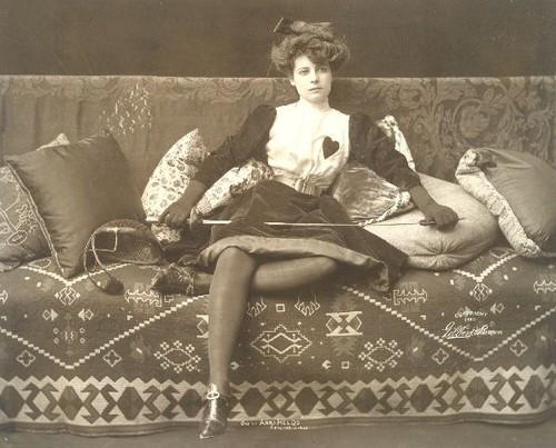 Ein antikes Foto von einer Frau in Fechtkleidung, auf einem Sofa, mit Florett in der Hand.