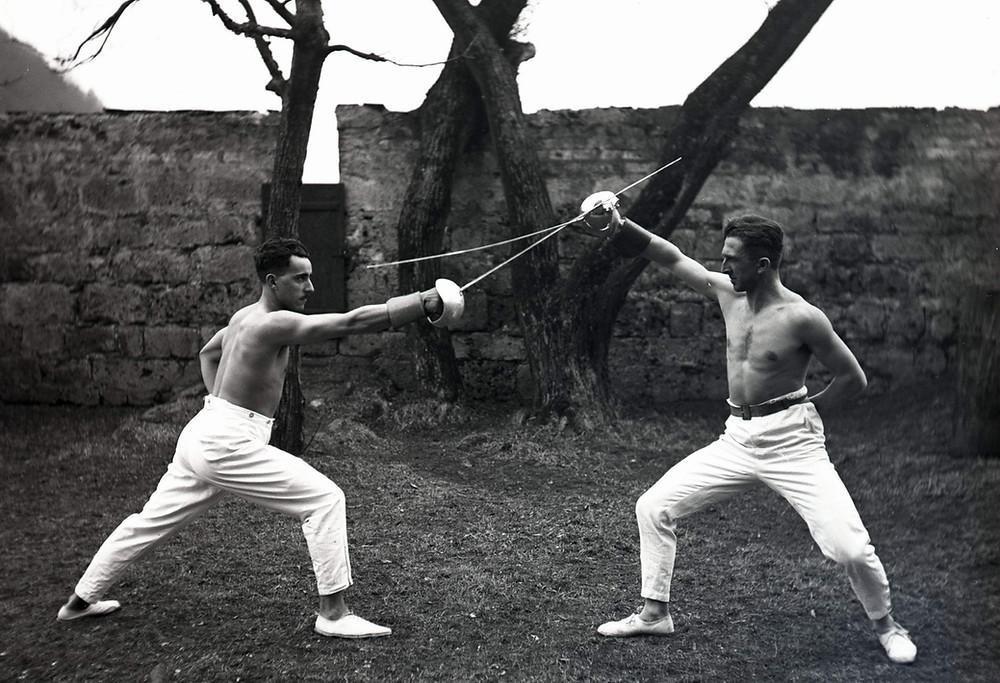 Ein altes Foto von zwei Säbelfechtern mit freiem Oberkörper.