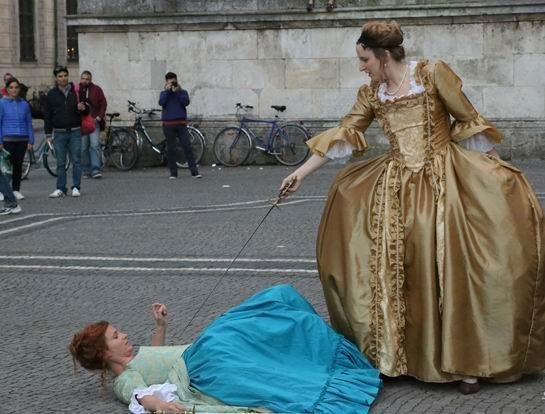 Szenisches Gefecht, eine Fechterin liegt am Boden, eine andere bedroht sie mit dem Hofdegen.