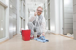 Man in Overall Cleaning Office Corridor.
