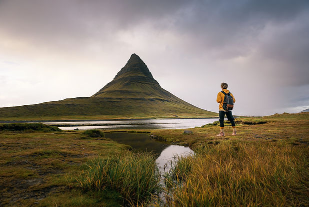 Young hiker with a backpack looks at the Kirkjufell mountain in Iceland. This 463 m high m
