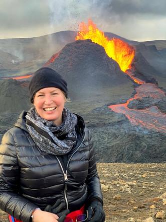 A woman smiling at the volcano fagradals