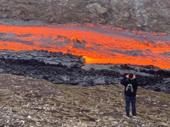 A person taking a picture of the magma at Fagradalsfjall Volcano_3x.jpg