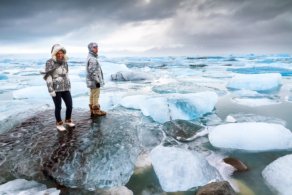 Extremely beautiful tourists stand on the massive icebergs in lake Jokulsarlon in Iceland