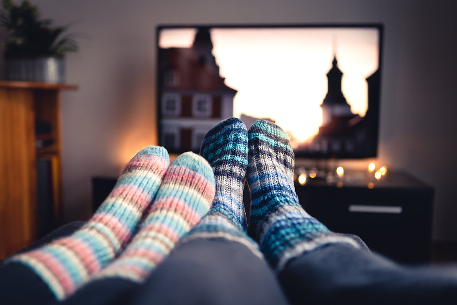 Couple with socks and woolen stockings watching movies or series on tv in winter. Woman an