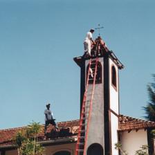 Funcionários fazem o acabamento da torre de nossa capela