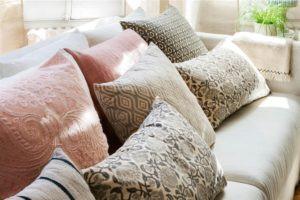 cojines-en-rosa-gris-y-verde-con-estampados-florales-y-bordados-sobre-sofa-blanco_1000x667_008ac50a