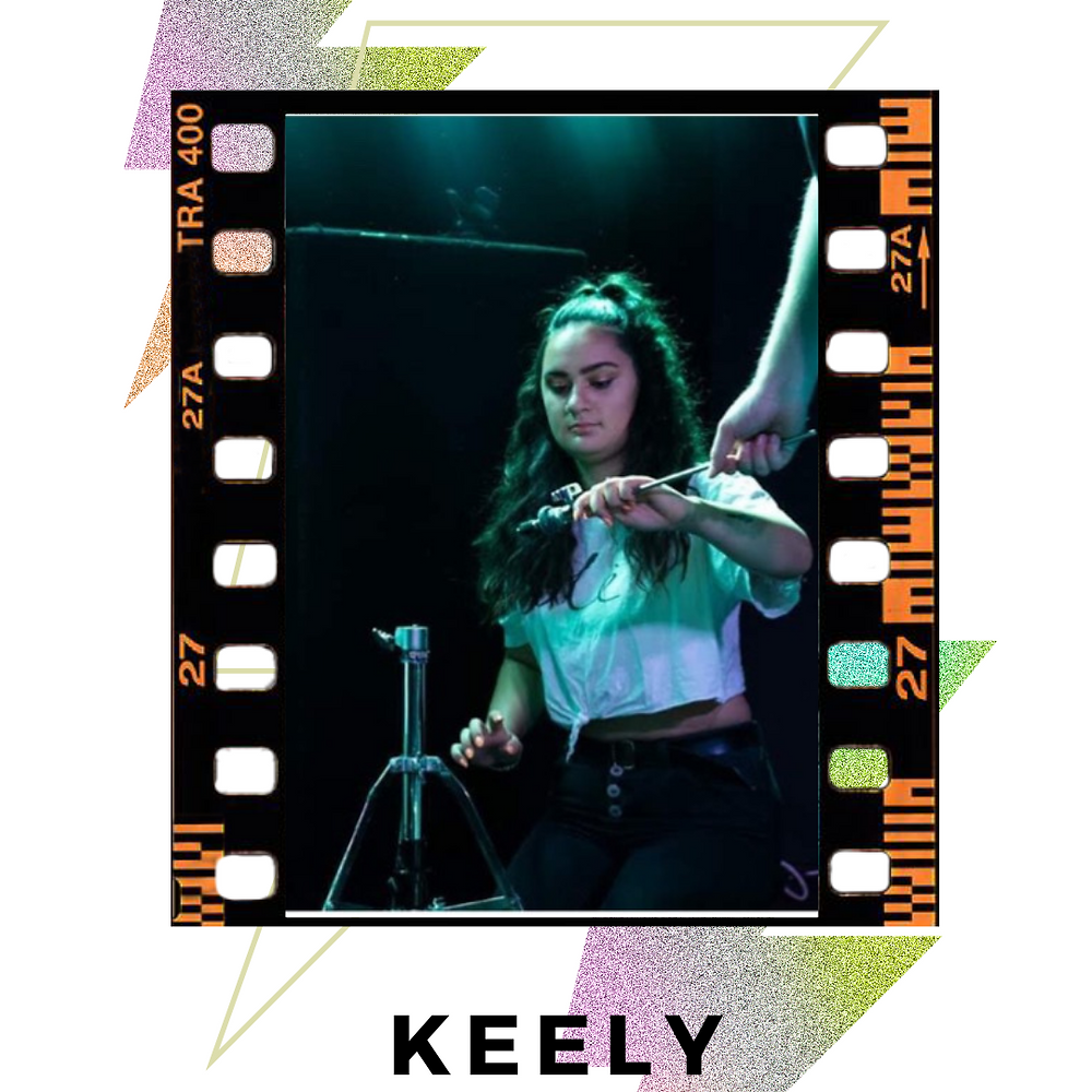 Keely is crouching on the floor assembling a drum set. Image is bordered with  black film and decorative/colourful lighting bolds behind image.  Text: Keely