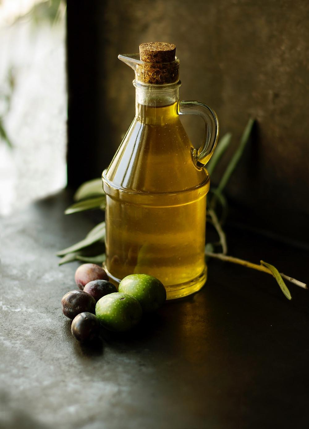 Mit einem Korken verschlossene Glasflasche gefüllt mit Olivenöl