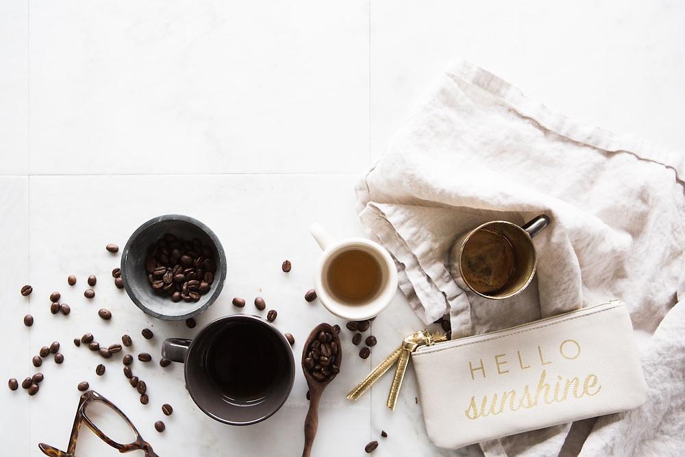 Kaffeebohnen und Kaffeetassen. Die Bohnen liegen verstreut herum.