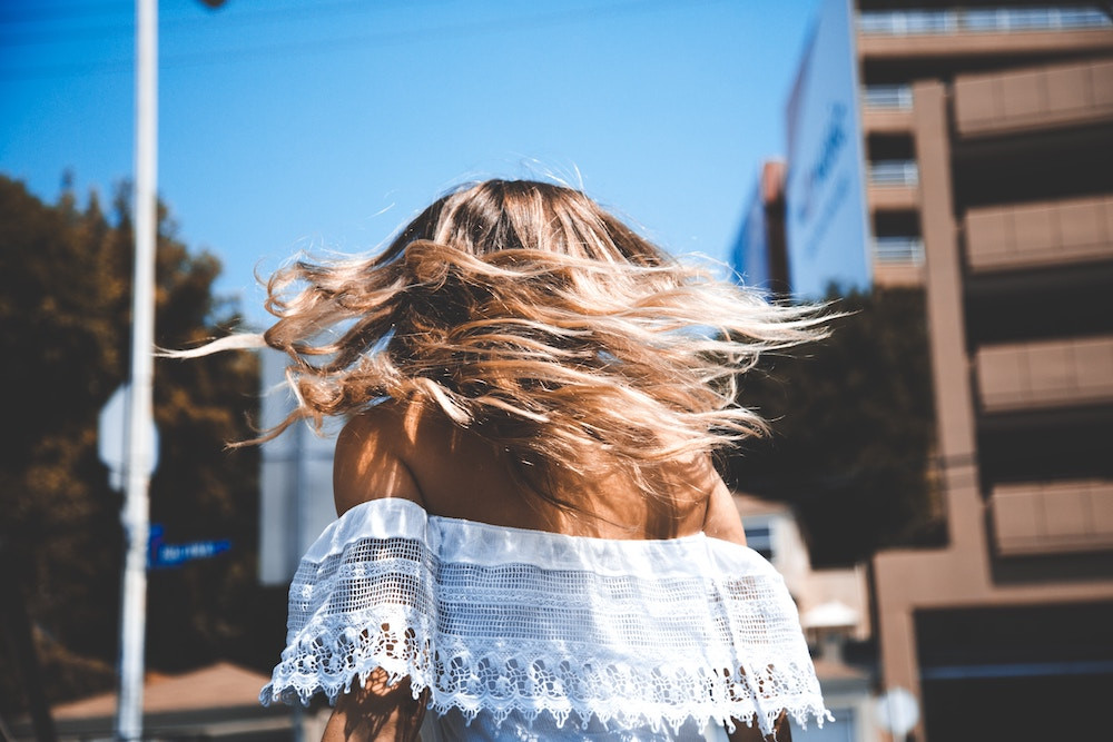 Junge Frau mit blondem Haar bei blauem Himmel