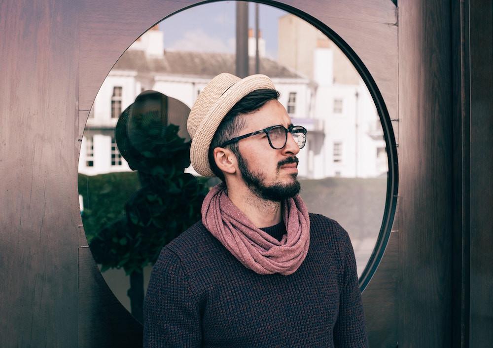 Dunkelhaariger Mann mit Brille und Hut