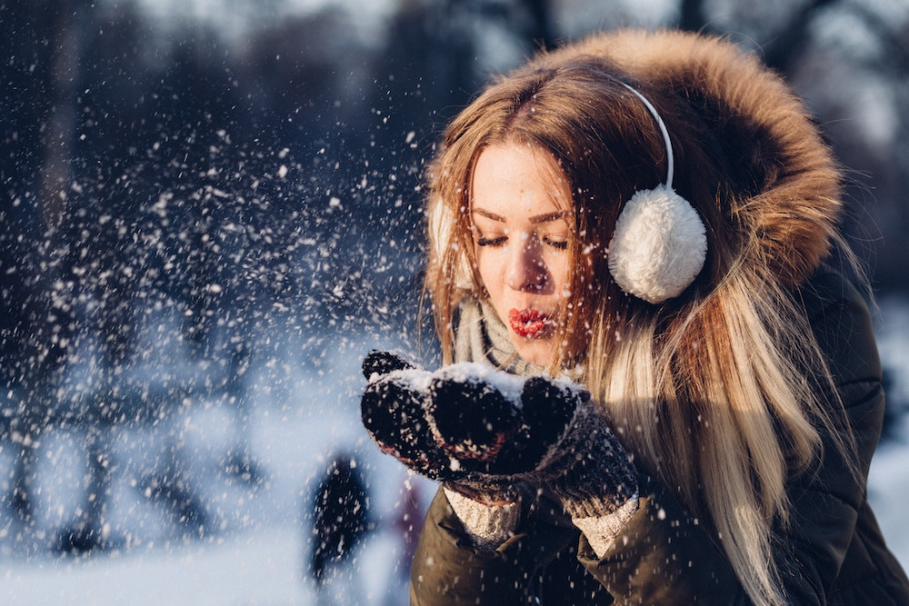 Frau blaest Schnee von den Haenden