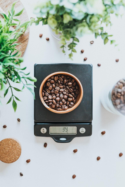 Kaffeebohnen in einer Schale auf einer Küchenwaage.