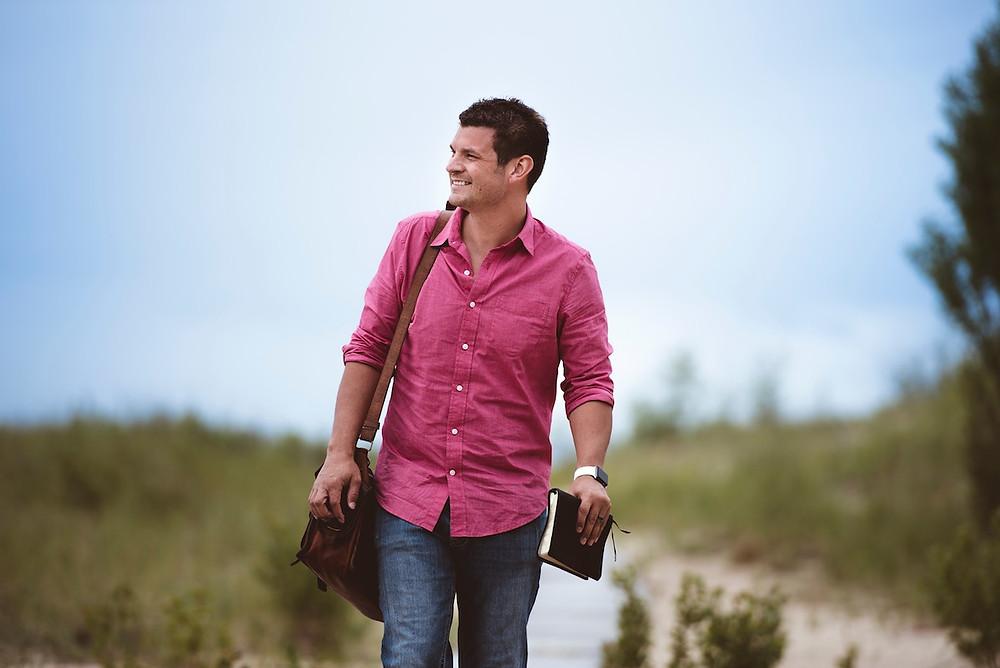 Mann mit rosa Hemd und Schultertasche