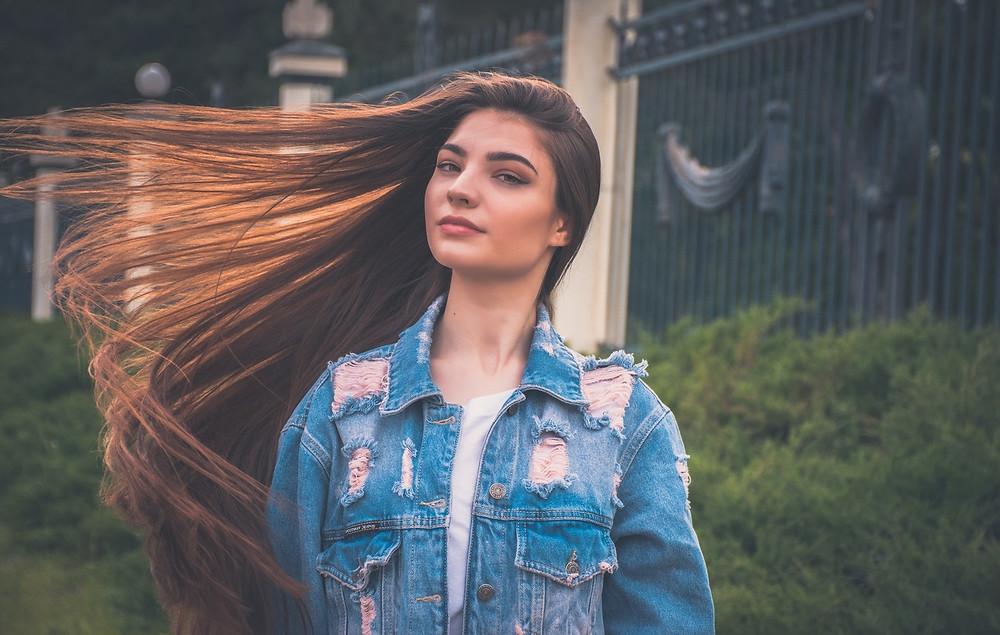 Junge Frau mit geschwungenen, langen braunen Haaren.